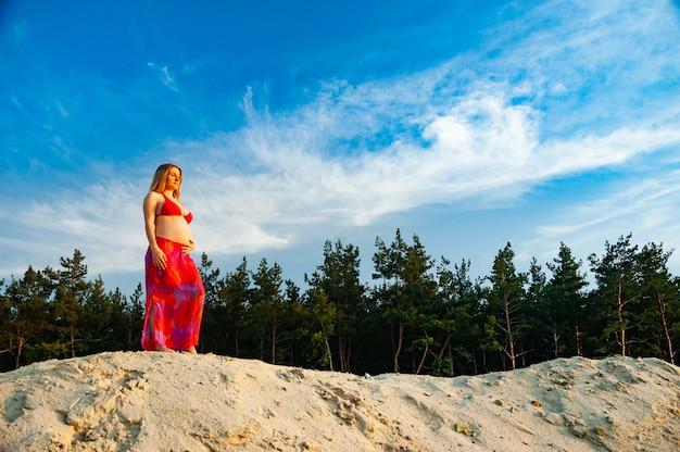 Schöne junge schwangere frau mit einem nackten bauch geht in der natur nahe dem wald und see.