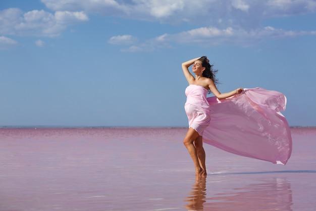 Schöne junge schwangere frau, welche die sonne am strand, rosa see genießt