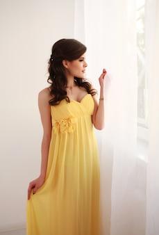 Schöne junge schwangere frauen, die durch das fenster im gelben langen kleid schauen