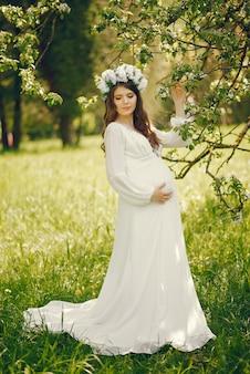 Schöne junge schwangere mädchen in einem langen weißen kleid und kranz auf dem kopf