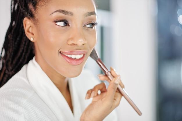 Schöne junge schwarze frau, die erröten oder gesichtspuder vor dem spiegel anwendet