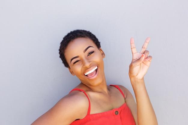 Schöne junge schwarze frau, die mit friedenshandzeichen lächelt