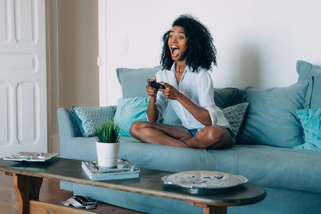 Schöne junge schwarze frauensitzplätze im sofa, das videospiele spielt