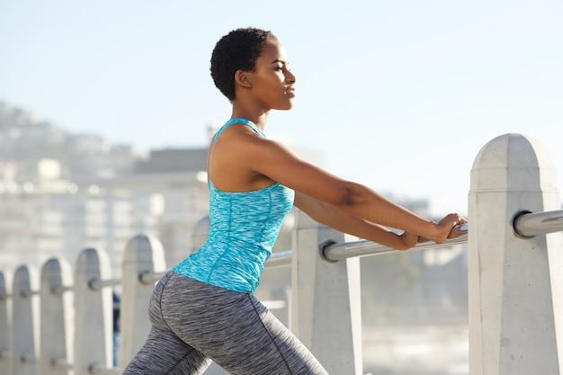 Schöne junge schwarze sportfrau, die auf dem geländer draußen sich lehnt