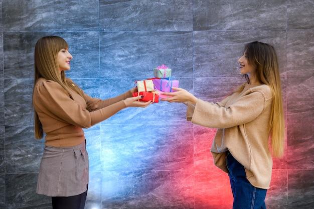 Schöne junge schwestern. weihnachts- und neujahrsfeier. zwei schöne schwestern tauschen sich mit geschenkboxen aus