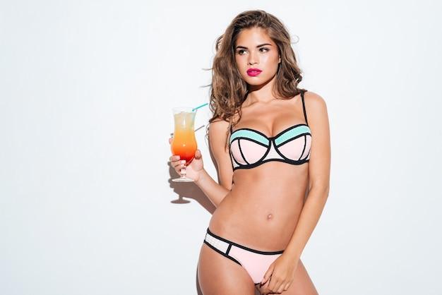 Schöne junge sexy frau, die cocktail trägt bikini lokalisiert auf dem weißen hintergrund hält