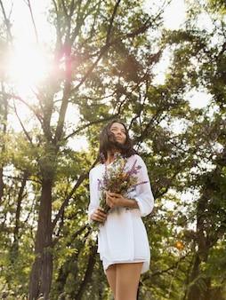 Schöne junge sexy frau im weißen kleid, das wildblumen am ländlichen sonnigen hintergrund sammelt