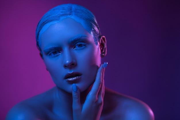 Schöne junge sexy frau in neonblau lila lichter