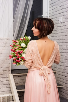 Schöne junge sexy frau mit einem großen strauß tulpen in einem hotelzimmer