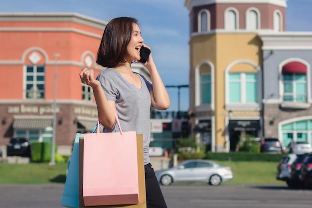 Schöne junge shopaholic asiatin, die smartphone für die unterhaltung verwendet