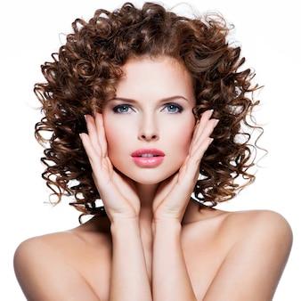 Schöne junge sinnliche frau mit brünettem lockigem haar, das ihr gesicht durch hände auf weißer wand berührt.