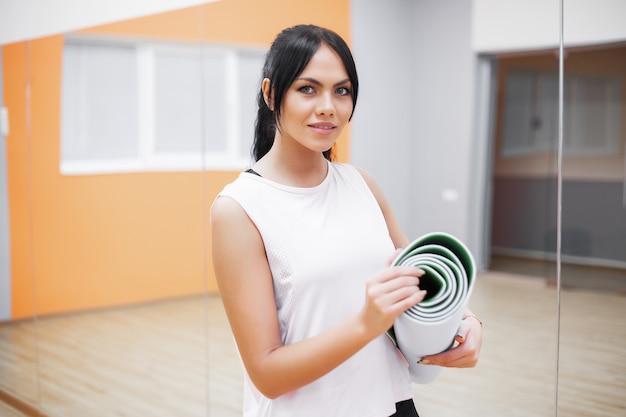 Schöne junge sporteignungsfrau machen die übungen, die eignungwolldecke halten