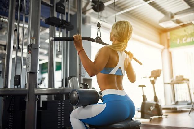 Schöne junge sportfrau, die im fitness-studio aufwirft
