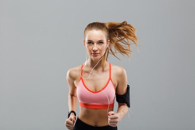 Schöne junge sportfrau, die isolierte hörende musik durch kopfhörer läuft.