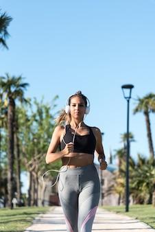 Schöne junge sportfrau, die joggen in einem park draußen musik hört läuft