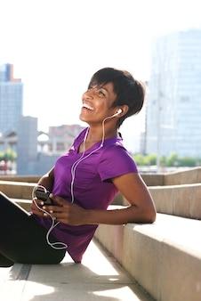 Schöne junge sportfrau, die mit kopfhörern und handy auf treppe sich entspannt
