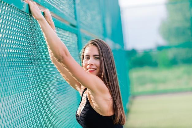 Schöne junge sportfrau gekleidet in einem bodysuit auf tennisplatz