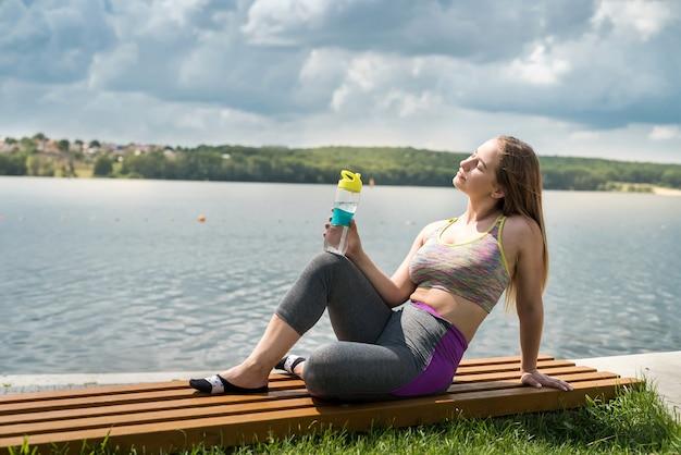 Schöne junge sportlerin, die am see nach dem training mit einer flasche wasser in der hand ruht