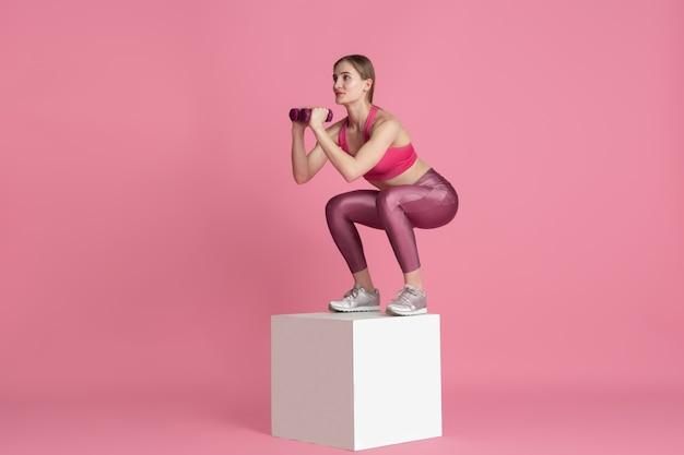 Schöne junge sportlerin, die auf einfarbigem porträt der rosa wand übt