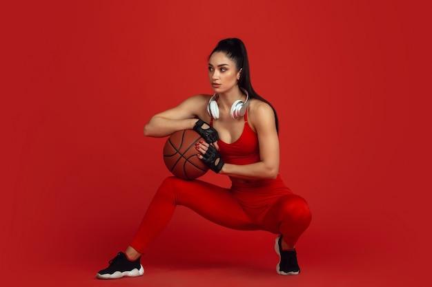 Schöne junge sportlerin, die auf einfarbigem porträt der roten wand übt