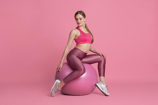 Schöne junge sportlerin, die auf rosa studio übt