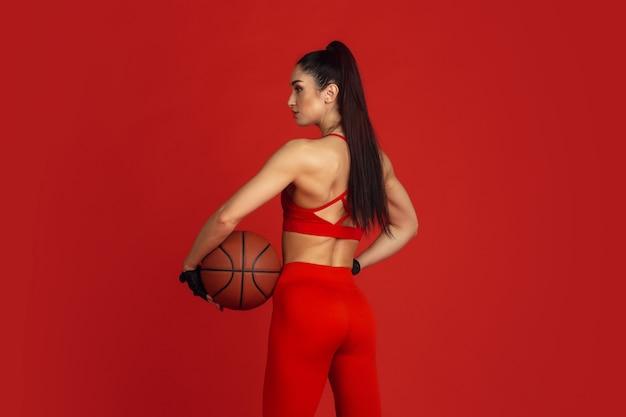 Schöne junge sportlerin, die im studio übt, monochromes rotes porträt.
