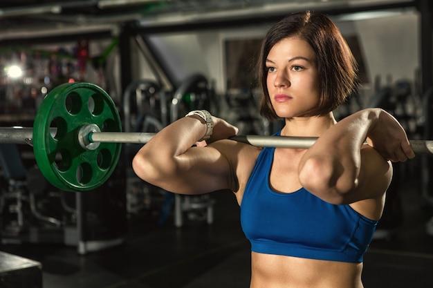 Schöne junge sportlerin, die mit schwerer langhantel im fitnessstudio trainiert