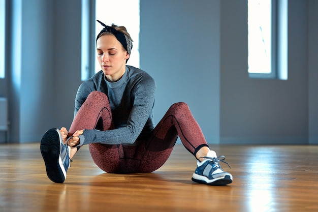 Schöne junge sportlerin, die schnürsenkel an turnschuhen bindet, während sie sich vom krafttraining im fitnessstudio entspannt. außer fitness und sport