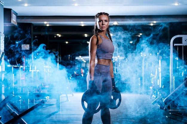 Schöne junge sportlerin im fitnessstudio