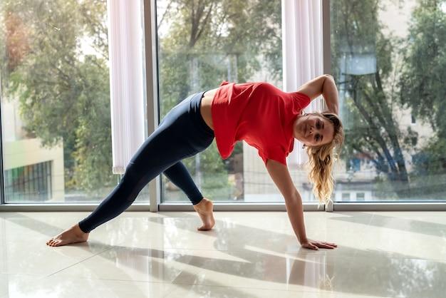 Schöne junge sportliche frau, die yoga für gesundheit zurück praktiziert. sport als lebensstil