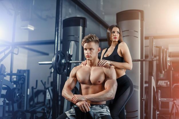 Schöne junge sportliche sexy paare, die muskel und training in der turnhalle während des photoshooting zeigen
