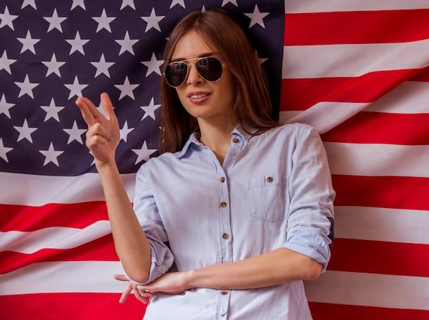 Schöne junge steht gegen die amerikanische flagge.