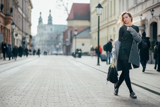Schöne junge stilvolle blonde frau, die grauen mantel, dunkelgrünes kurzes kleid und schwarze strumpfhosen trägt, die durch krakauer stadtstraßen gehen. platz für text.