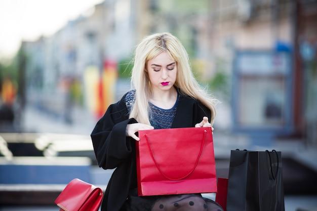 Schöne junge stilvolle blonde frau im schwarzen mantel mit einkaufstaschen, die auf einer bank im park sitzen