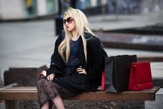 Schöne junge stilvolle blonde frau im schwarzen mantel und in der sonnenbrille mit einkaufstüten, die auf einer bank im park sitzen