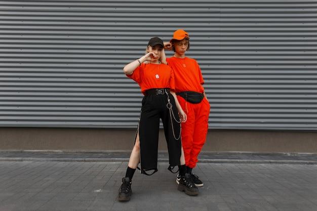 Schöne junge stilvolle frau mit einem schönen jungen mann in modischer orange stilvoller kleidung mit kappen, die nahe der grauen metallwand aufwerfen. modepaar