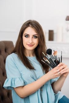 Schöne junge stilvolle frau mit make-up-bürsten in den händen