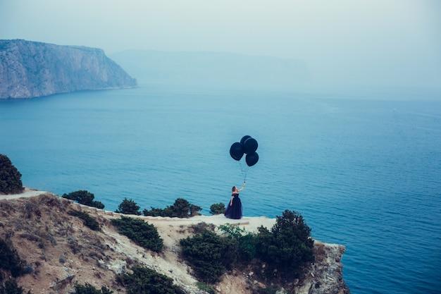 Schöne junge stilvolle frauen mit ainbow ballons in den händen gegen den himmel. die idee der konfrontation und die einheit der gegensätze. dunkel und hell. die leidenschaft und zärtlichkeit