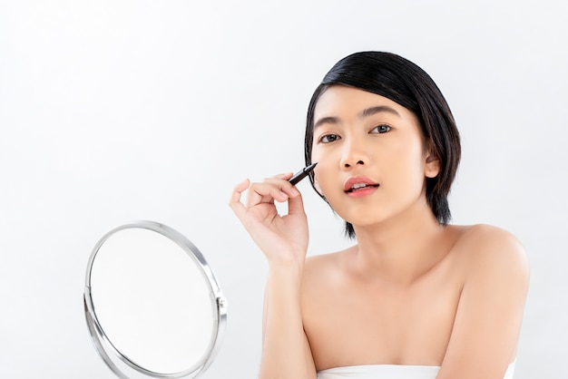 Schöne junge strahlende haut asiatin, die eyelinermake-up hält