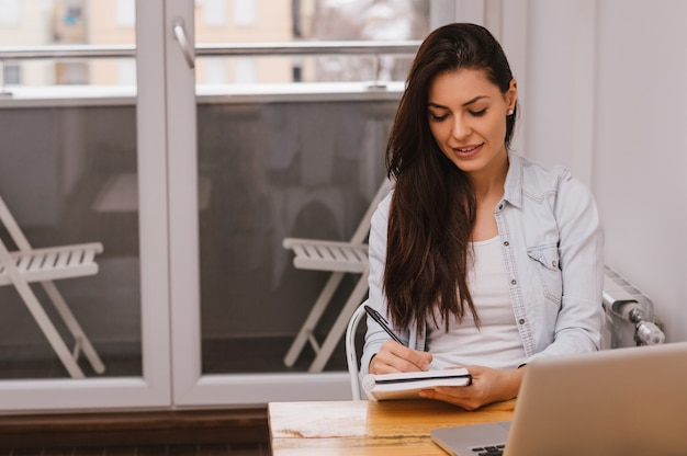 Schöne junge studentenschreibenshausarbeit unter verwendung des laptops und des buches