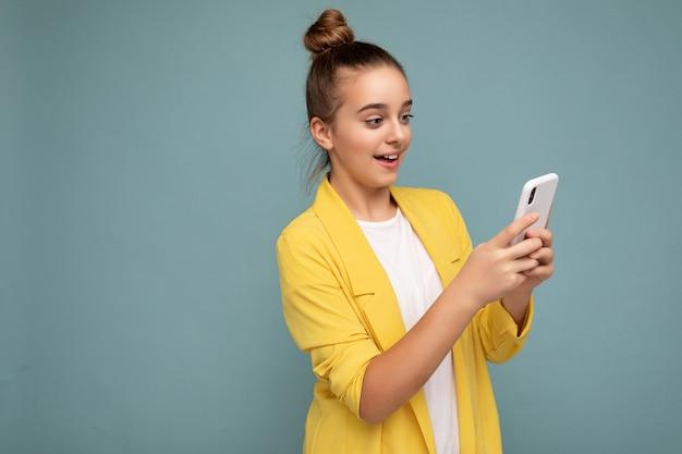 Schöne junge teenager in freizeitkleidung, die isoliert über dem hintergrund steht und per telefon im internet surft und auf den mobilen bildschirm schaut.