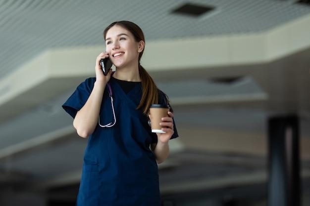 Schöne junge therapeutische ärztin, die mit laptop und dokumenten vor dem arbeitstisch sitzt