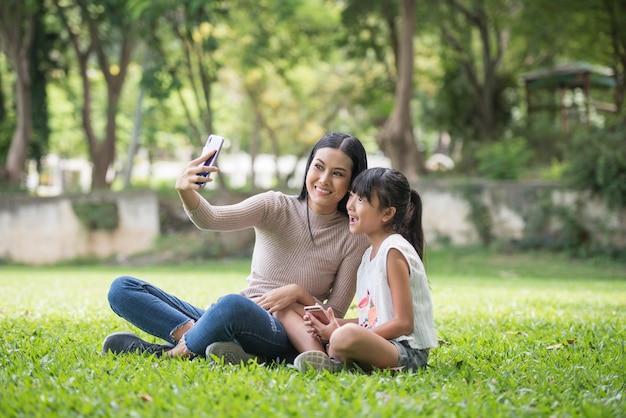 Schöne junge tochter, die draußen intelligentes telefon mit ihrer mutter am park verwendet