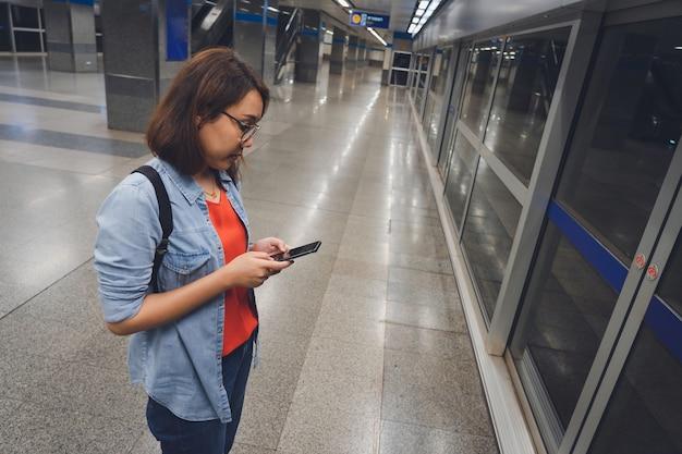 Schöne junge touristen, die auf die u-bahn wartend stehen, zusammen mit intelligenten telefonen