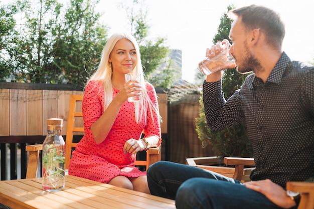 Schöne junge trinkende getränke des mannes und der frau