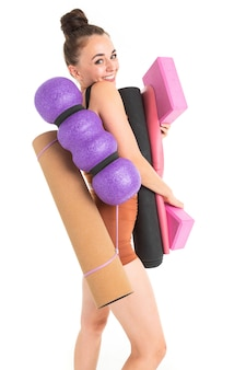 Schöne junge turnerin mit dunklem langem haar, gefüllt in einem bündel im braunen sportlichen elastischen anzug mit sportinventar