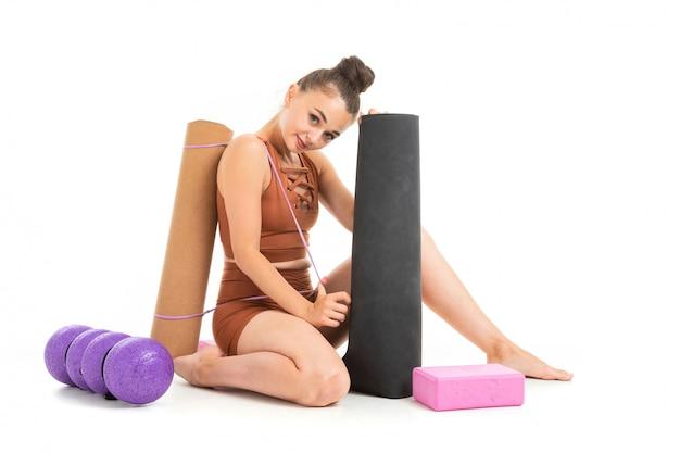 Schöne junge turnerin mit dunklem langem haar, gefüllt in einem bündel in braunem sportelastikanzug, sitzt mit sportinventar