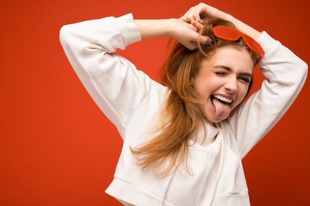 Schöne junge überglückliche blonde frau isoliert auf buntem hintergrund in lässigem weiß