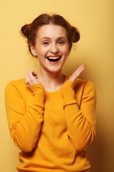 Schöne junge überraschte rothaarfrau über gelbem hintergrund