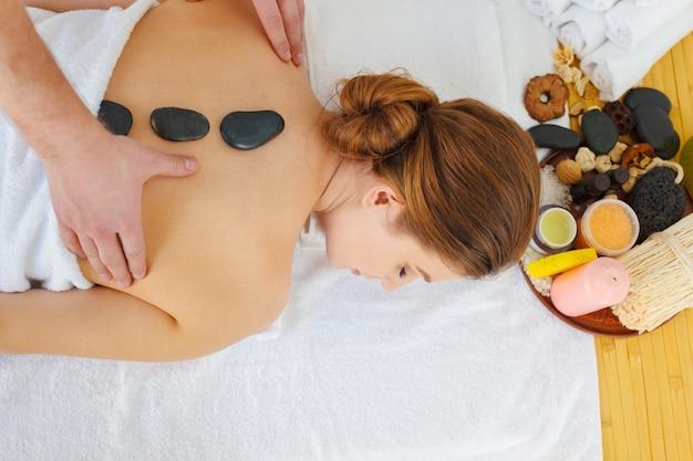 Schöne, junge und gesunde frau im badekurortsalon. massagebehandlung